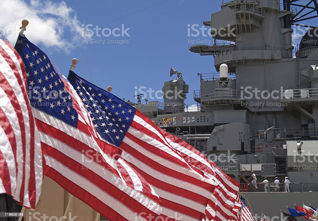 US Flags Beside Battleship Missouri Memorial with Four Sailors stock photo