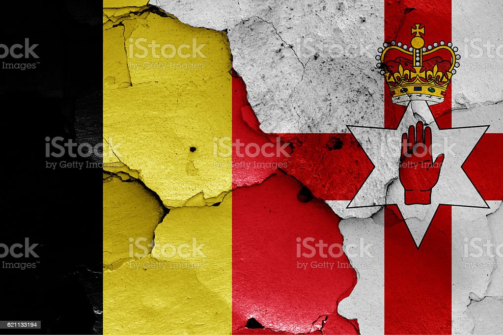 flags of Belgium and Northern Ireland painted on cracked wall stock photo