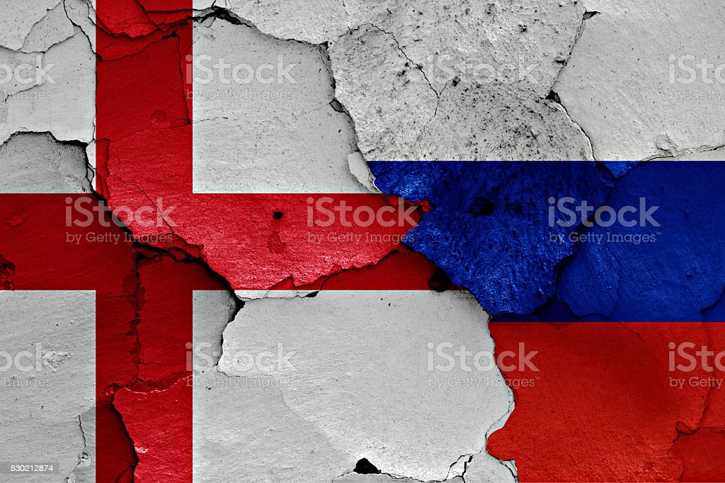 flags of England and Russia painted on cracked wall stock photo