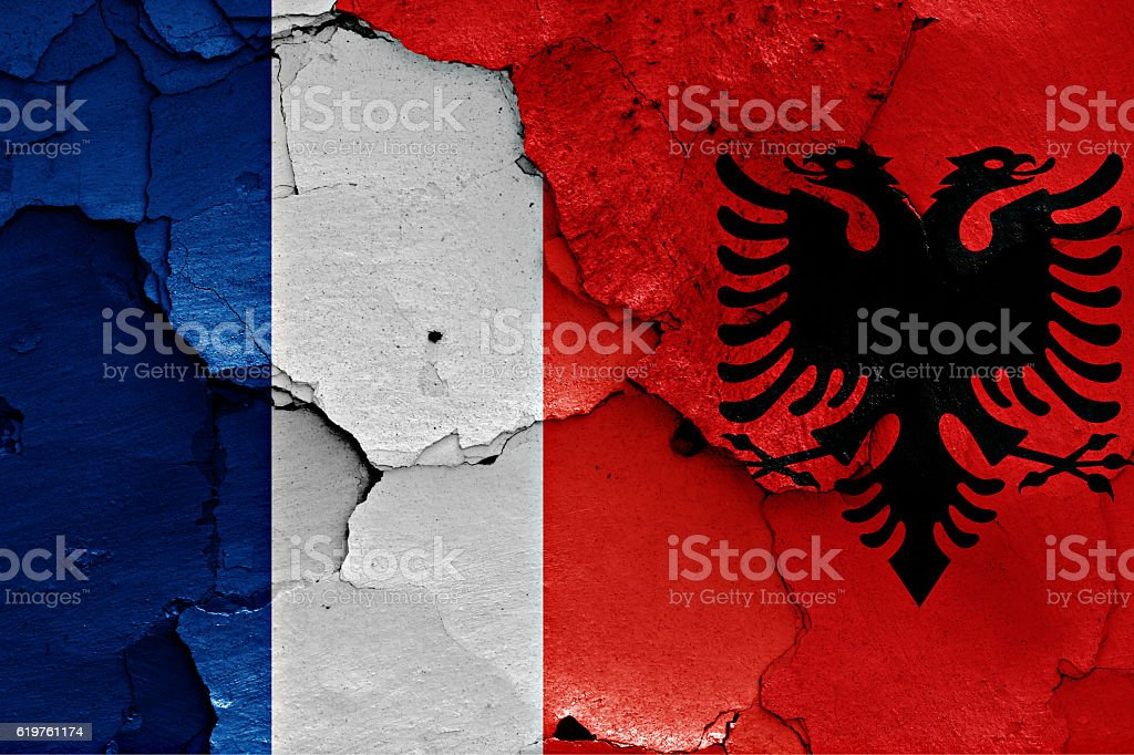 flags of France and Albania painted on cracked wall stock photo