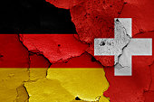 flags of Germany and Switzerland painted on cracked wall