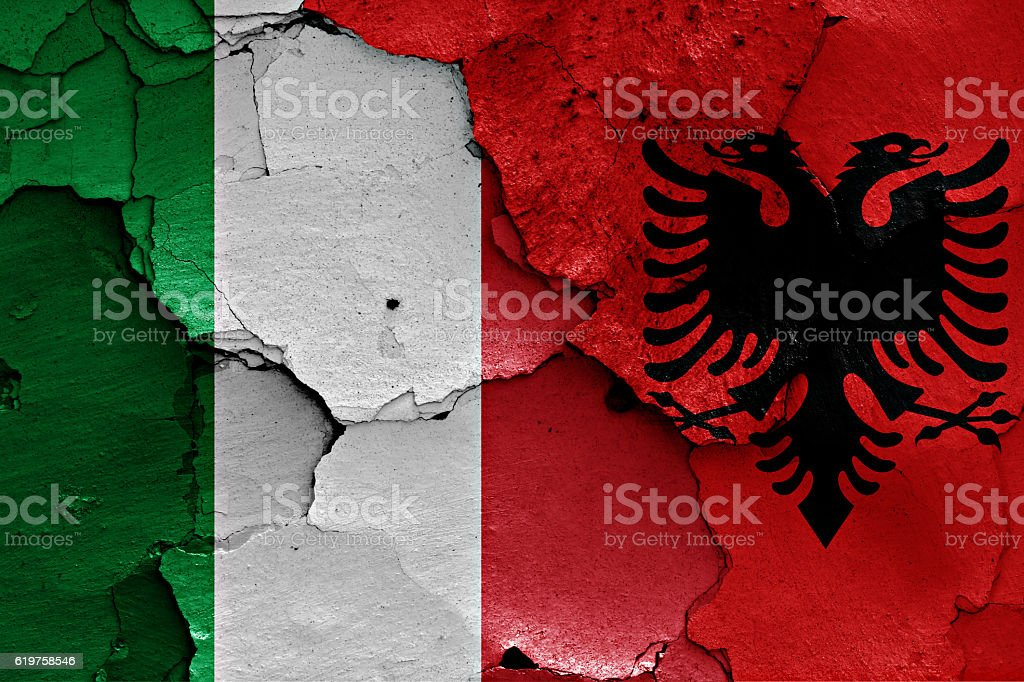 flags of Italy and Albania painted on cracked wall stock photo
