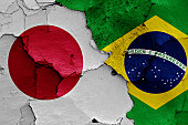 flags of Japan and Brazil painted on cracked wall