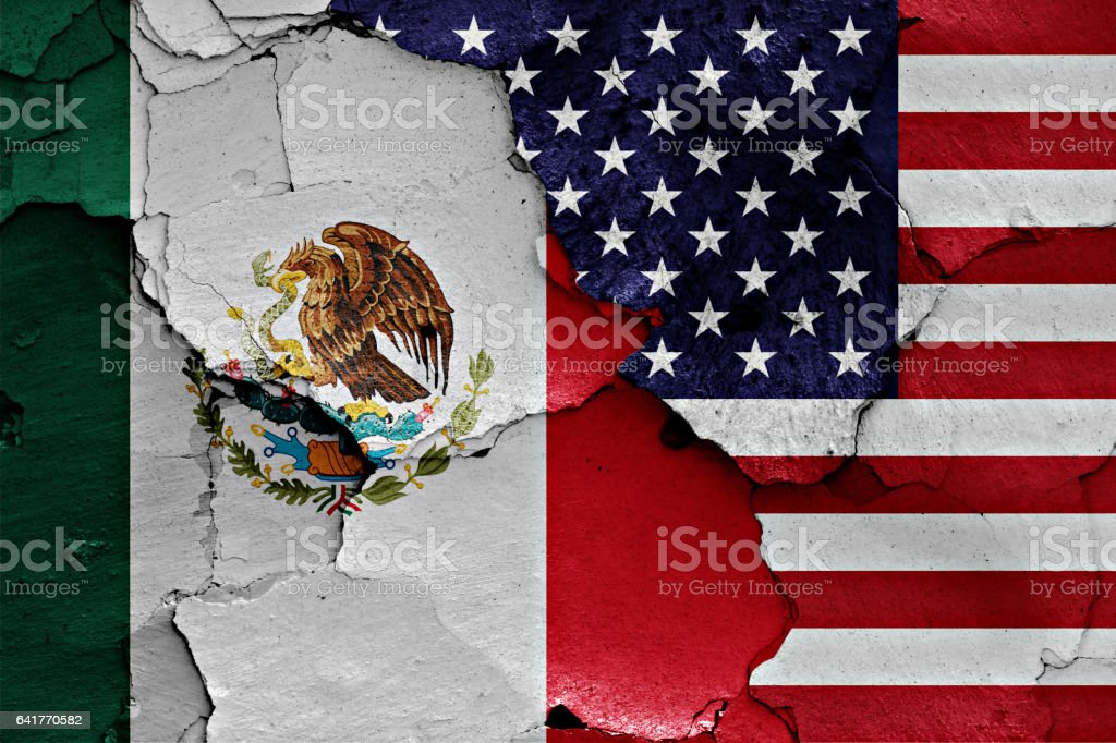 flags of Mexico and USA painted on cracked wall stock photo