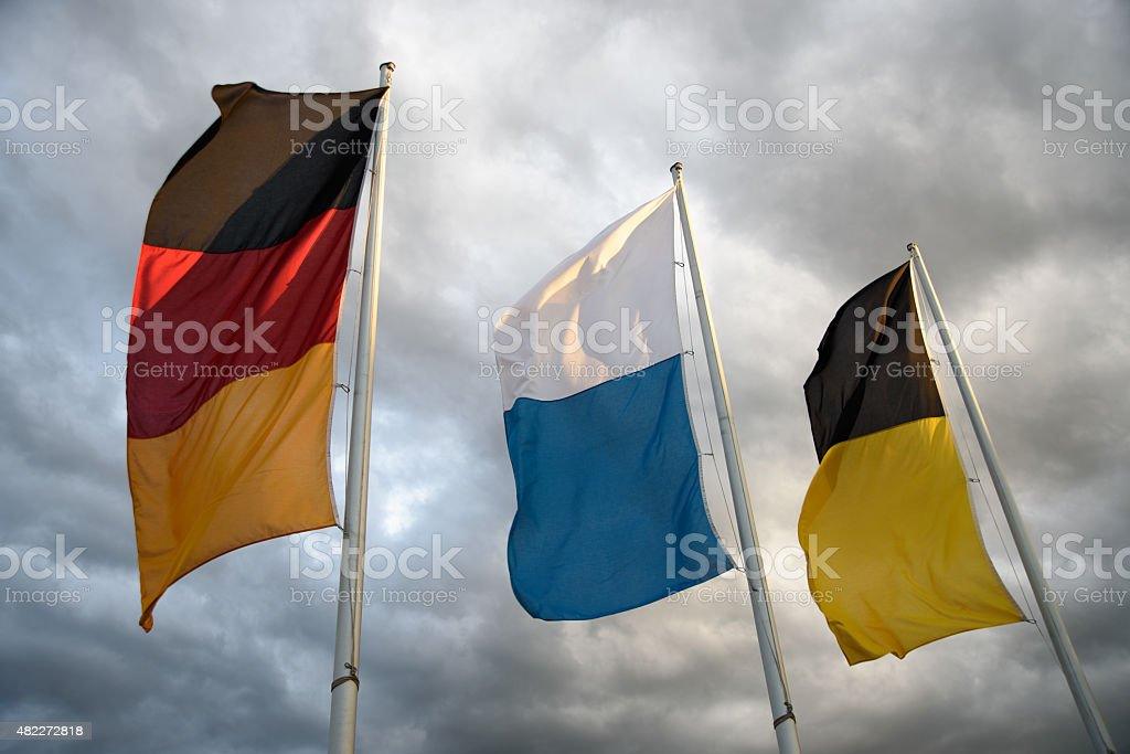 Flags of Munich, Bavaria and Germany before an upcoming storm stock photo