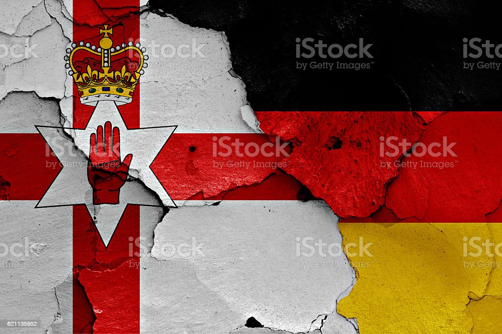 flags of Northern Ireland and Germany painted on cracked wall stock photo