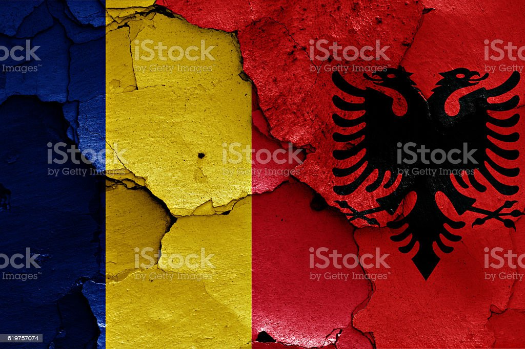 flags of Romania and Albania painted on cracked wall stock photo