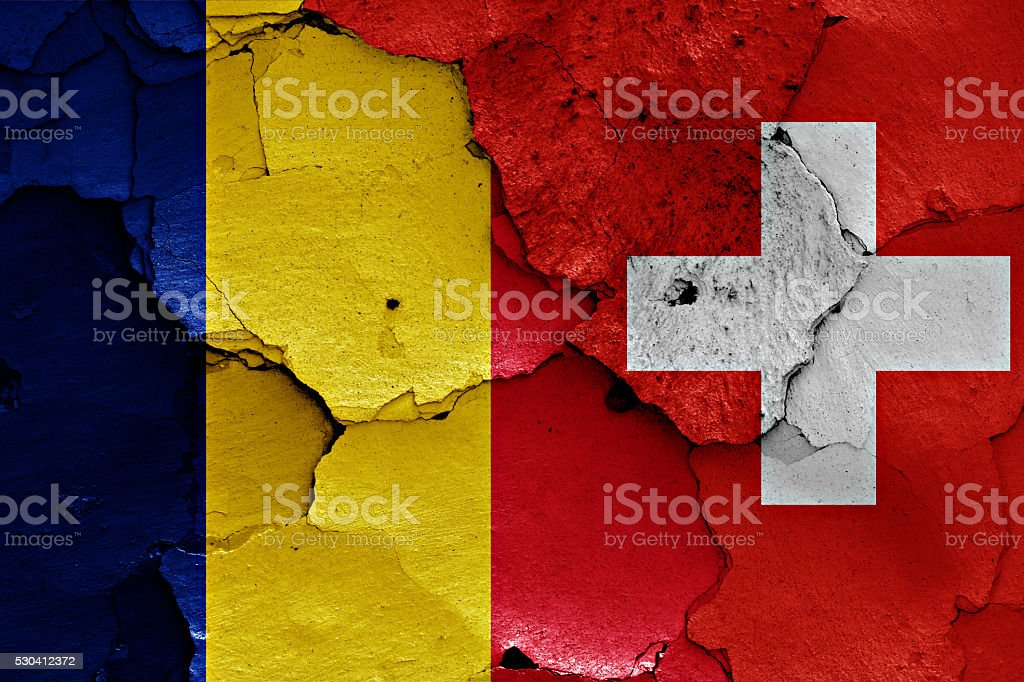 flags of Romania and Switzerland painted on cracked wall stock photo