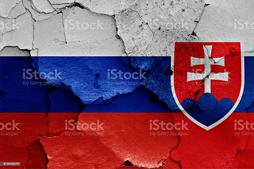flags of Russia and Slovakia painted on cracked wall stock photo