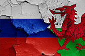 flags of Russia and Wales painted on cracked wall