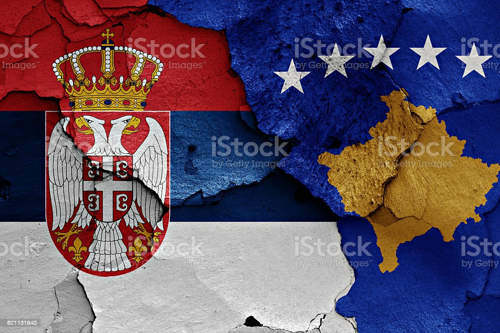 flags of Serbia and Kosovo painted on cracked wall stock photo