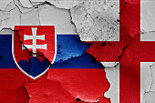 flags of Slovakia and England painted on cracked wall