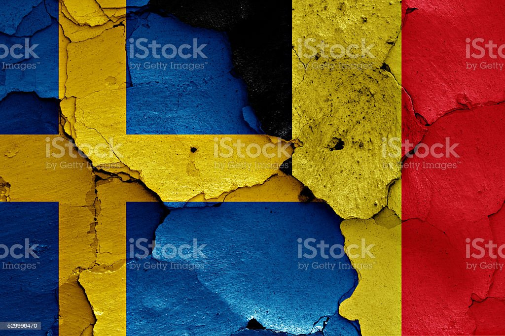 flags of Sweden and Belgium painted on cracked wall stock photo