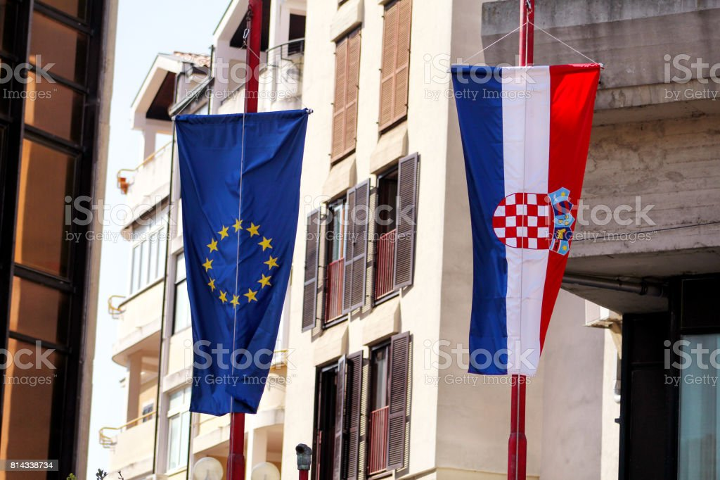 Flags of the European Union and Croatia on the street. In the background a detail of the building. Croatian and EU flag. stock photo