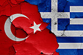 flags of Turkey and Greece painted on cracked wall