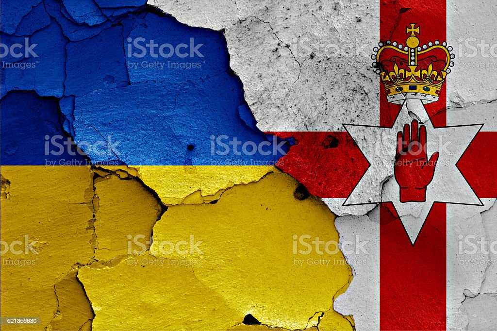 flags of Ukraine and Northern Ireland painted on cracked wall stock photo