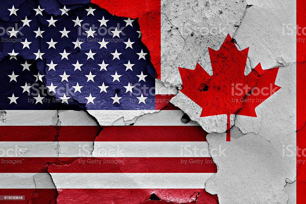 flags of USA and Canada painted on cracked wall stock photo