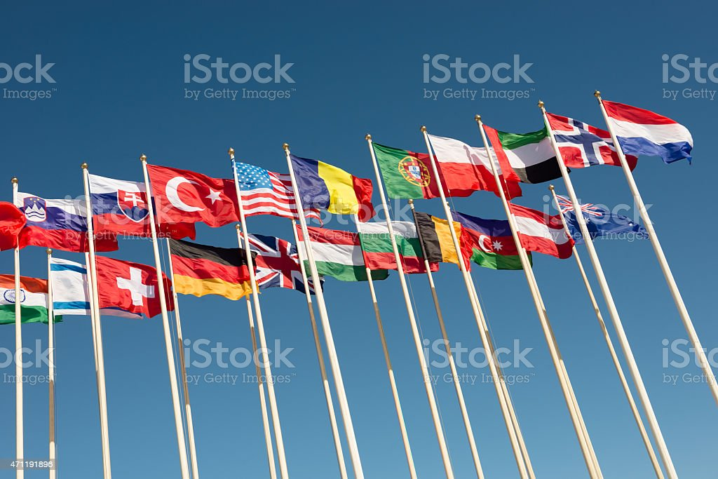 flags on flagpoles fluttering in the wind stock photo