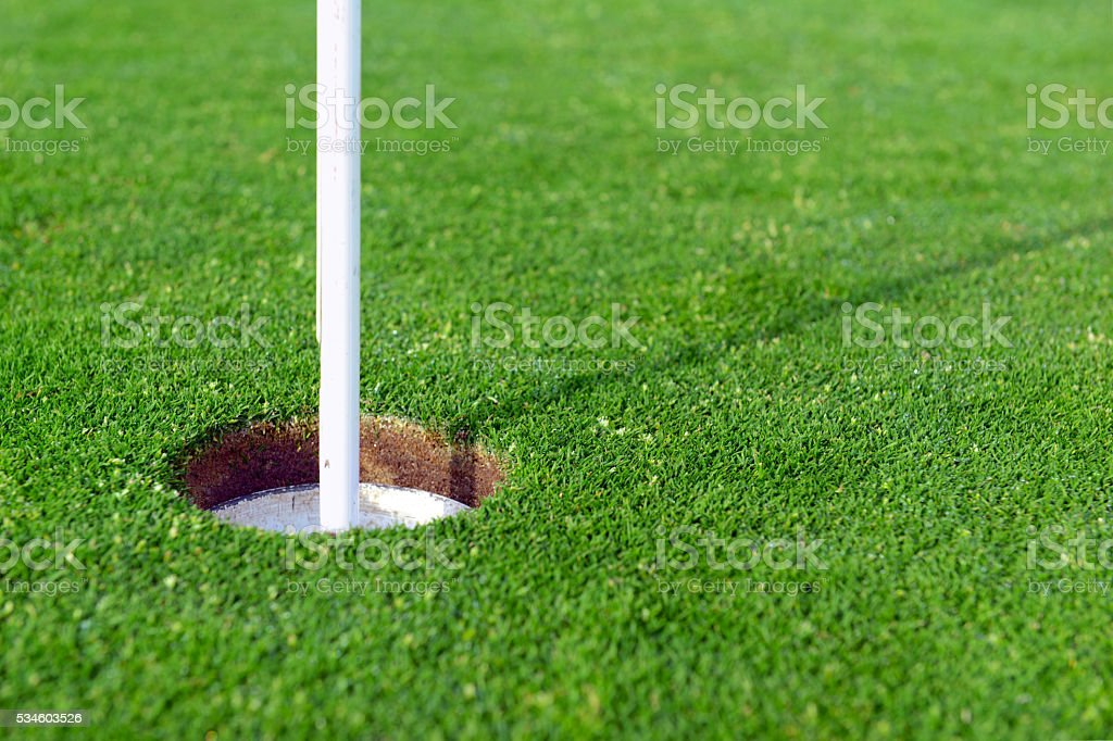 Flagstick Manicured grass of putting green of golf course stock photo