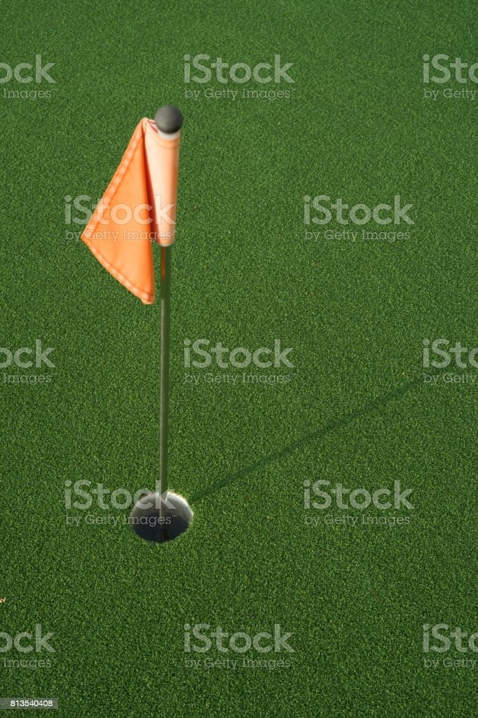 Flagstick with hole on green stock photo