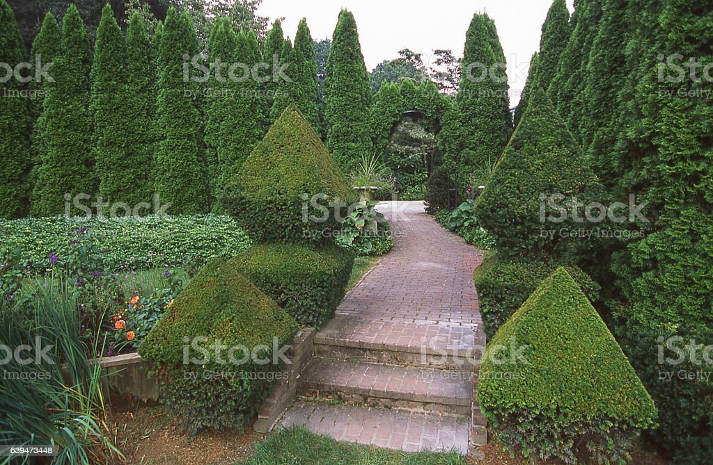 Flagstone path through landscaped gardens and topiary in Wilmington Delaware stock photo