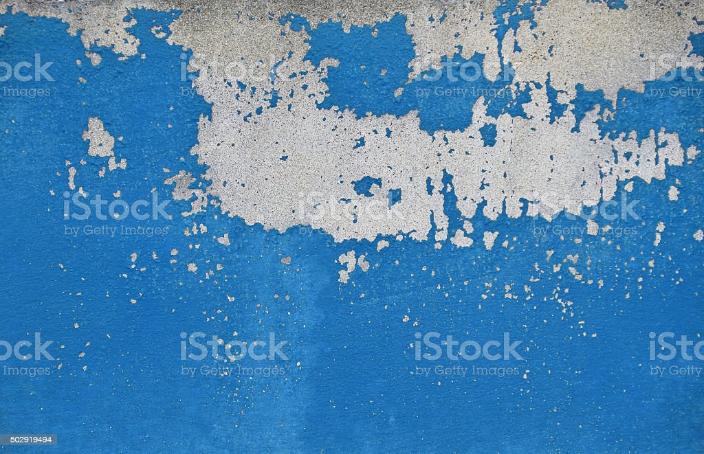 Flakes of old blue paint on grey concrete wall royalty-free stock photo