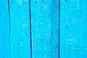 Flaking blue paint on old wooden boards