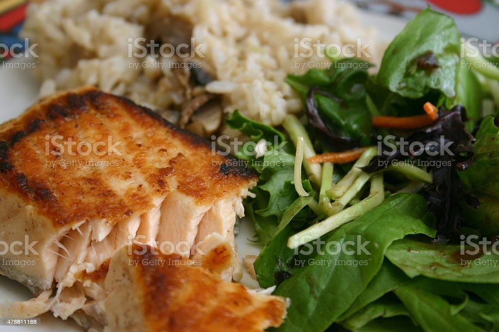 Flaky cooked salmon with salad and brown rice stock photo