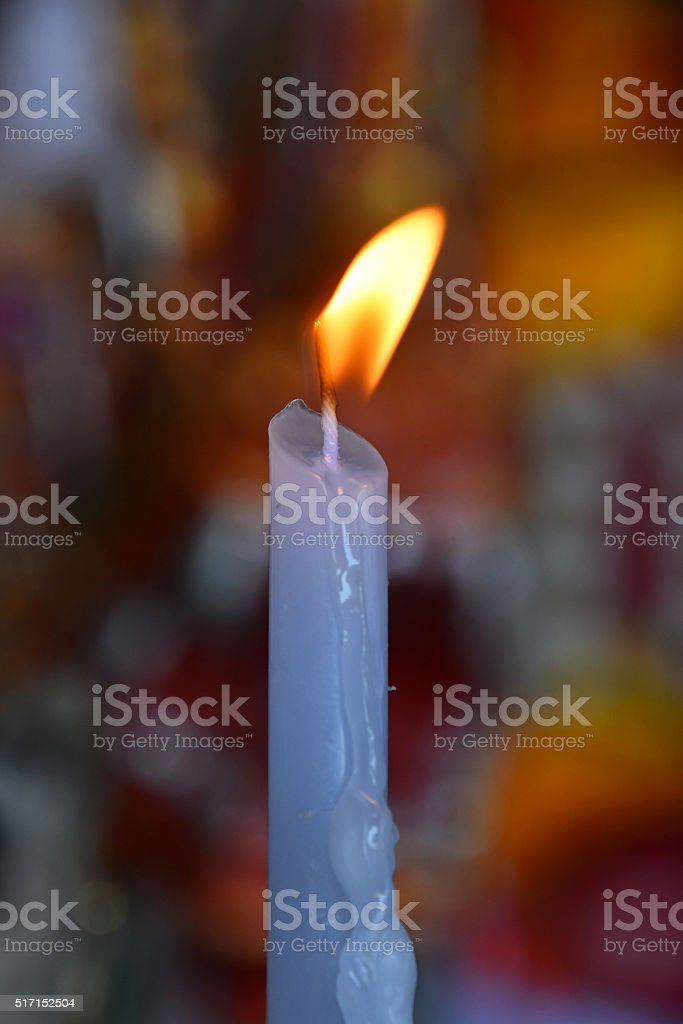 Flame of white melting candle in temple or church royalty-free stock photo