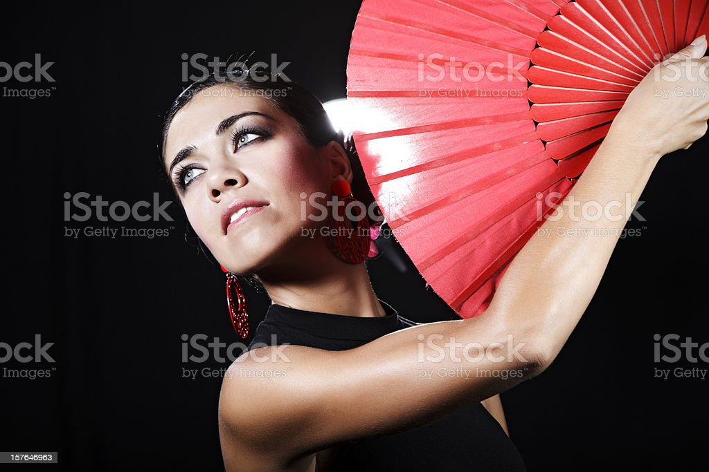 Flamenco dancer with red hand fan looking into the distance stock photo