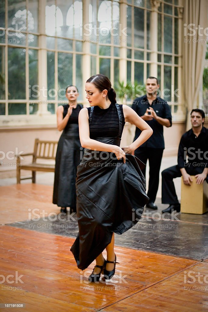 Flamenco female dancer performing with a group of singers. stock photo