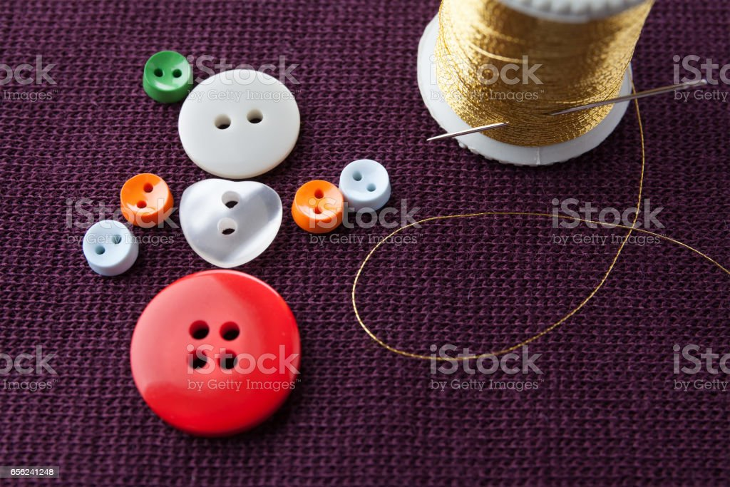 Flamenco girl conceptual design. Funny woman character made of colorful sewing buttons with needle and golden thread on violet textured textile background. macro view, shallow depth of field stock photo