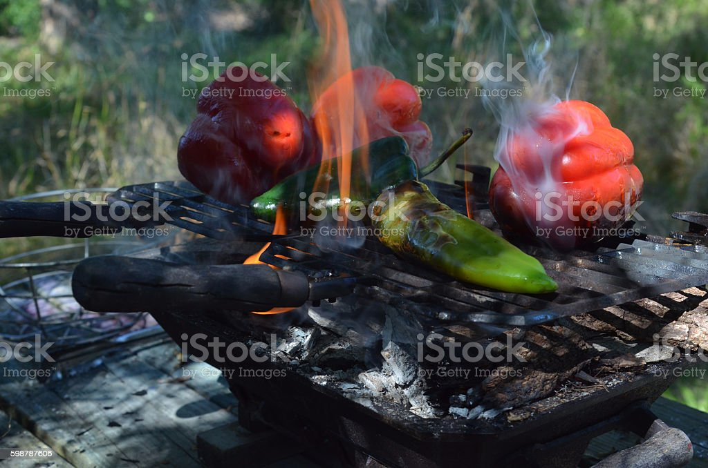 Flames and smoke grilling chili peppers, bell peppers stock photo