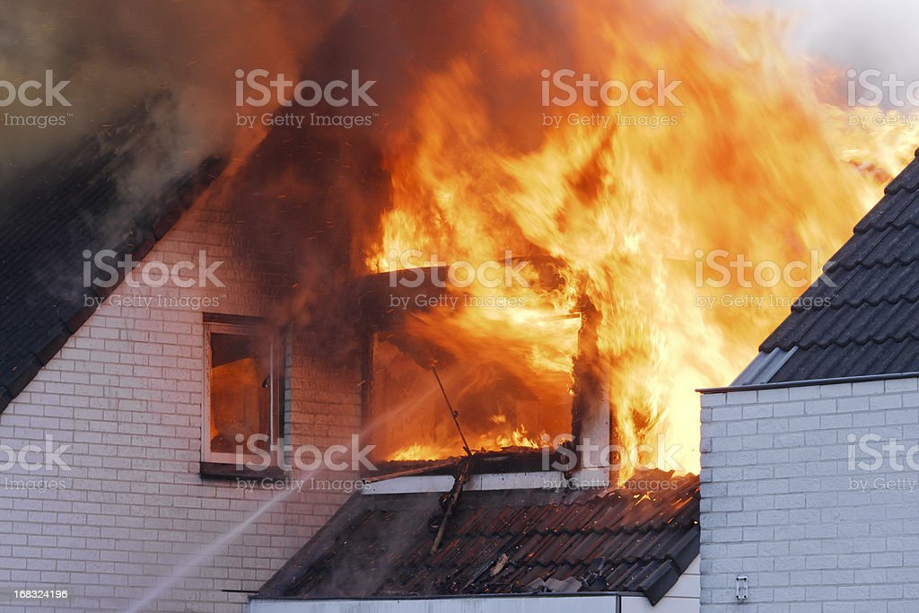 Flames coming out of white brick wall house on fire stock photo