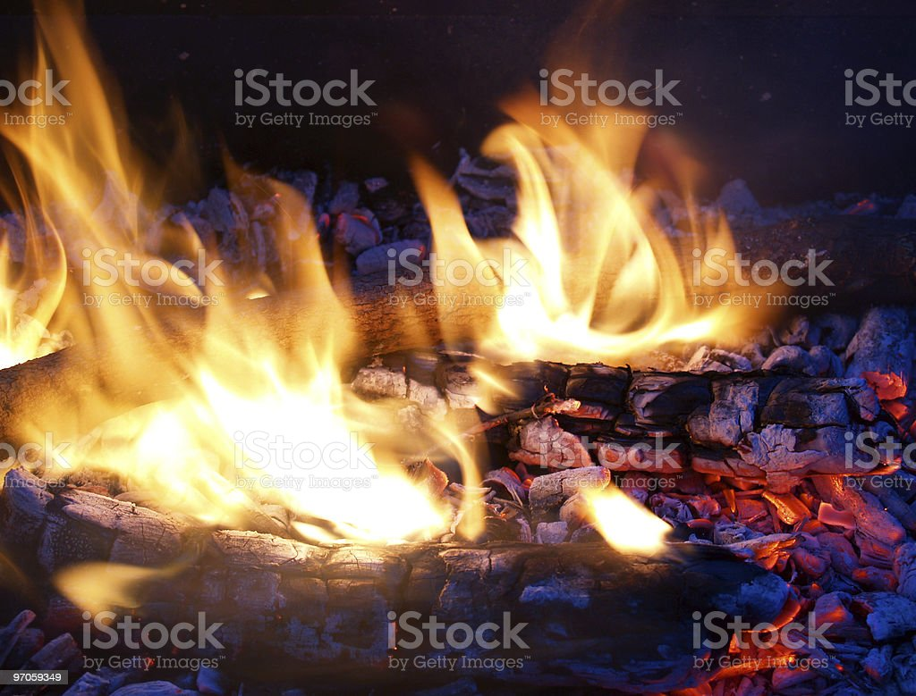 Flames in a fire pit with glowing embers royalty-free stock photo