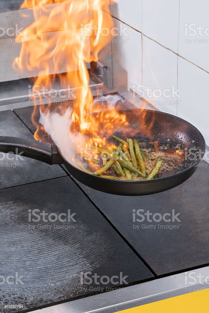 Flames in frying pan stock photo
