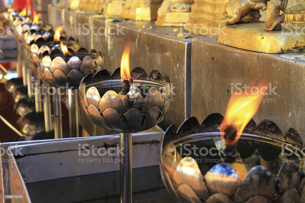 flames of oil lamps in a buddhist temple royalty-free stock photo