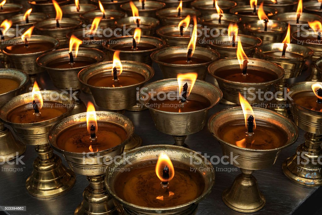 flames of oil lamps in temple stock photo