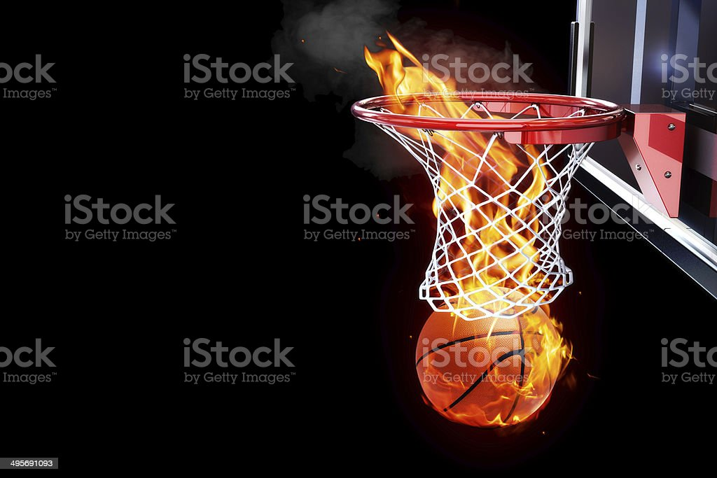 Flaming basketball going through a court net. stock photo