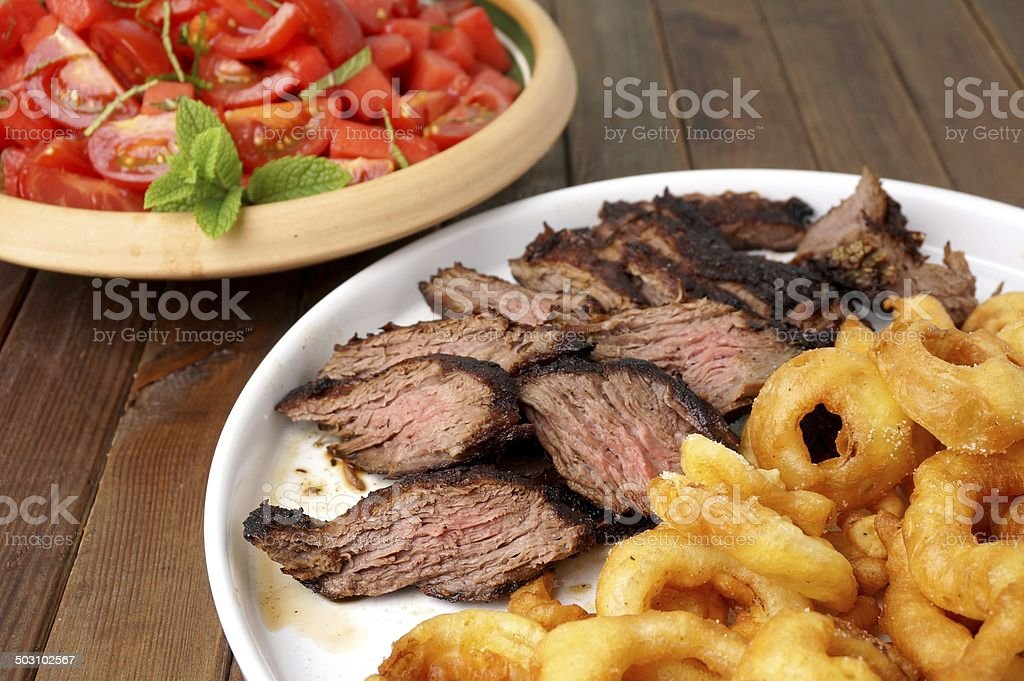 Flank steak with fries onion rings and salad royalty-free stock photo