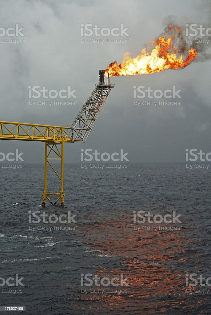 Flare boom nozzle and fire on offshore oil rig stock photo