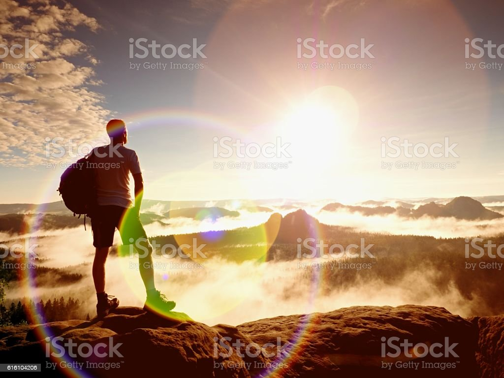 Flare. Lens reflections. Hiker in pants on cliff above valley. stock photo