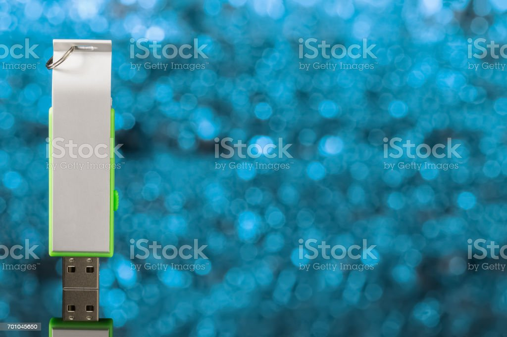 USB flash drive on a background out of focus and blue. Front view stock photo