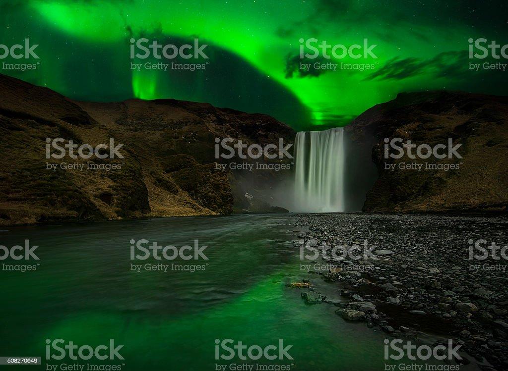 Flash of Aurora polaris above waterfall stock photo