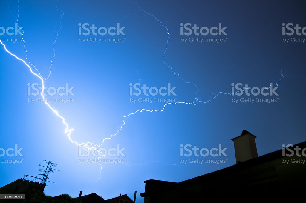 flash of lightning over housetops stock photo