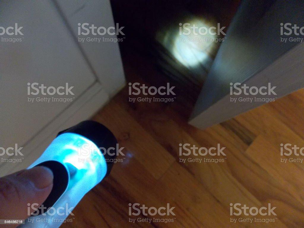 Flashlight Illuminating Dark Area Behind Door stock photo