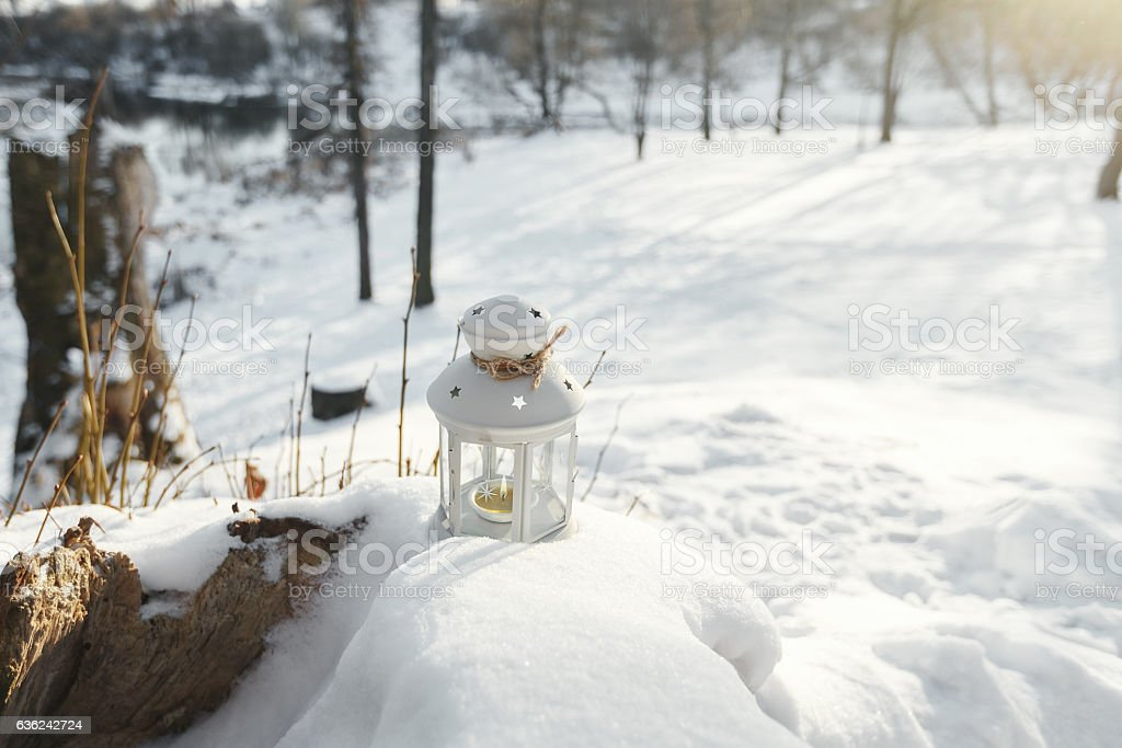 Flashlight inside burning candle standing in snow in winter stock photo