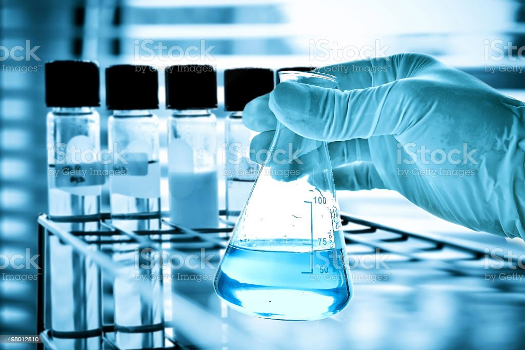 Flask and test tubes in scientist hand stock photo
