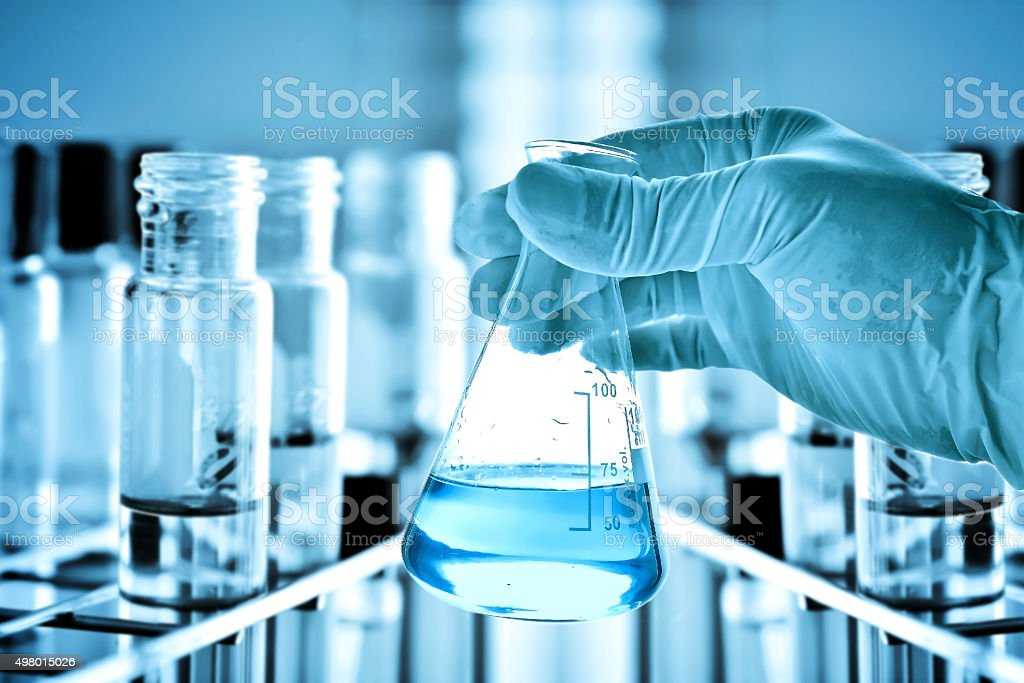 Flask in scientist hand and test tubes in rack stock photo