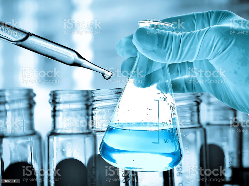 Flask in scientist hand and test tubes stock photo